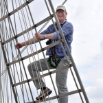 Man climbing the rigging of a tall ship.